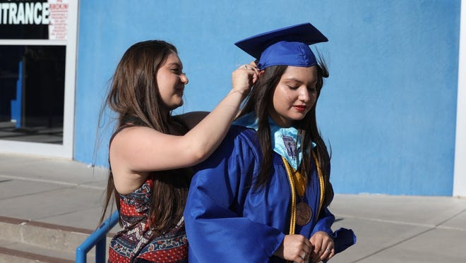 Bloomfield High School graduate Micaela Olivas gets a final adjustments from her sister Rachel before Friday's graduation ceremony.