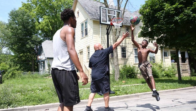 A Milwaukee Police officer plays basketball with kids near North 35th Street and West Custer Avenue after installing a new hoop.