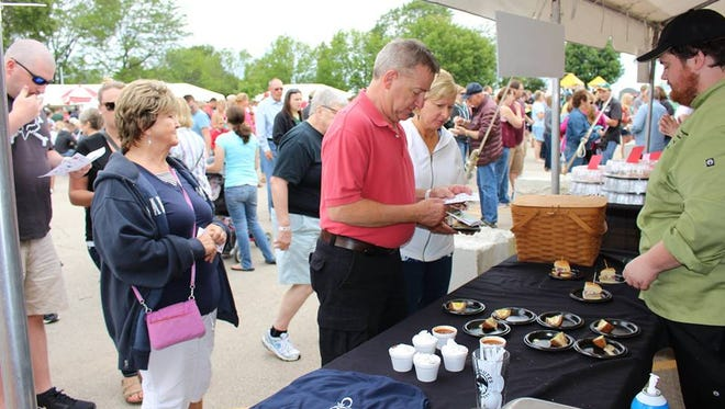 Festival goers lineup for a serving during the 2017 Taste of Fond du Lac held at Oven Island in Lakeside Park.