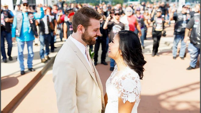 Michael Taylor and Amanda Zang are approached by Bikers For Christ on the John Seigenthaler Pedestrian Bridge hours before their wedding.
