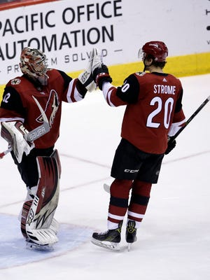 Arizona Coyotes goaltender Antti Raanta (32) celebrates with Dylan Strome (20) after shutting out the St. Louis Blues 5-0 during an NHL hockey game, Saturday, March 31, 2018, in Glendale, Ariz. (AP Photo/Rick Scuteri)