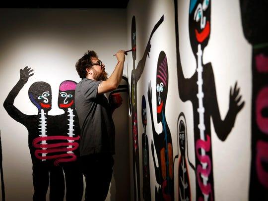 Artist Johnny Beaver works on the solar eclipse mural