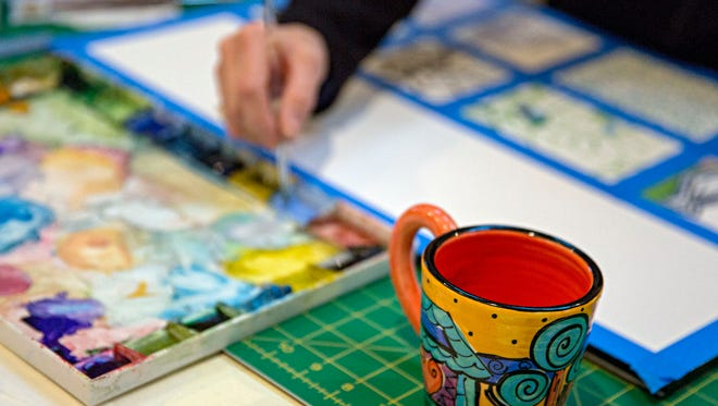 A cup of coffee sits nearby as Susie Phillips fleshes out pieces from her sketchbook. Phillips, an artist, works out of her Lakewood home outside Dallas and adheres to a regular routine to take advantage of morning hours, when she says she feels most creative and productive.