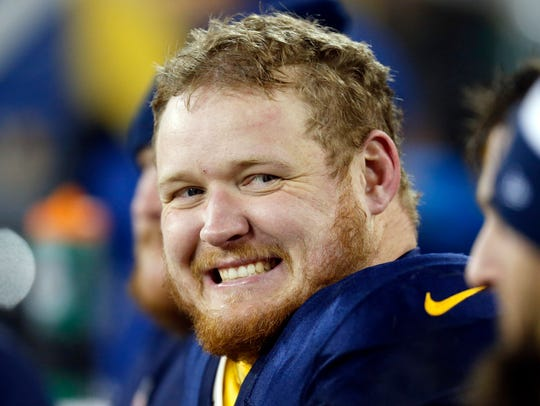 T.J. Lang smiles on the bench during the second half