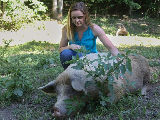 Danielle Priess, owner of Reed of Grace Farm, pets