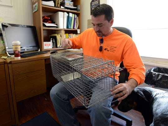 Corey Schoonover demonstrates how to use one of the Fairfield Area Humane Society's traps to collect stray cats. The traps can be rented by people who take part in the group's catch neuter and return program.