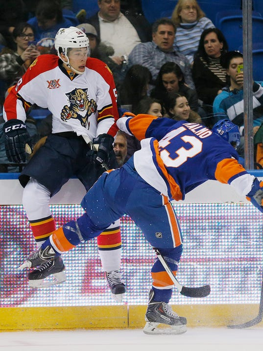 New York Islanders left wing Mike Halmo (43) sends Florida Panthers defenseman Jonathan Racine (58) into the boards on a check during the second period of an NHL hockey game at Nassau Coliseum in Uniondale, N.Y., Tuesday, April 1, 2014. (AP Photo/Paul J. Bereswill)
