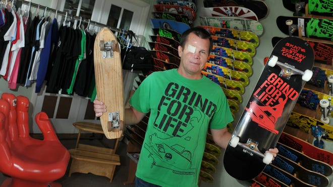Holding up an old skateboard from the 1960s and a newer model. Mike Rogers founded of Grind For Life, Inc. in 2003 after surviving his second battle with sarcoma cancer. Their mission is to provide travel expenses for cancer patients and families, which often is not covered by insurance.They are located in Cocoa Beach. The skateboards in the background arethe one that he sends as part of care packages of support to young people battling cancer.