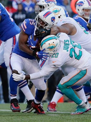Buffalo's LeSean McCoy (25) is hit by Dolphins defensive tackle Ndamukong Suh (top) and safety Reshad Jones (20). But McCoy had 112 yards rushing in Miami's 33-17 loss.