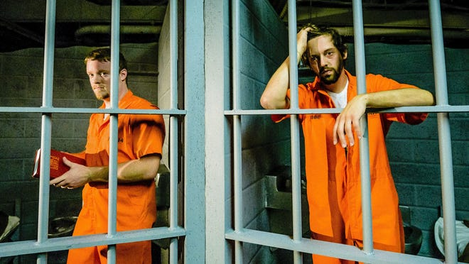 "Ben Guenther (left) as inmate Bobby Reyburn and Michael Banghart as John Brennan in the Lansing Community College production of ""Coyote on a Fence."""