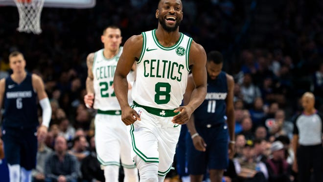 Boston Celtics guard Kemba Walker (8) smiles as he runs down the court after making a 3-pointer during the second half of the team's NBA basketball game against the Dallas Mavericks on Wednesday, Dec. 18, 2019, in Dallas.