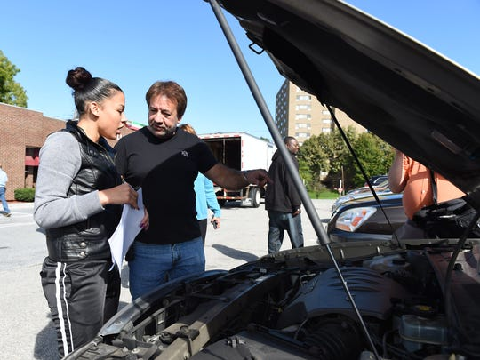 Lester Runza, right, owner of Lester's Auto Sales & Towing, which supplies the cars used in the Wheels for Work program, shows car recipient Trista Moseley, 19, left, how her new car runs.