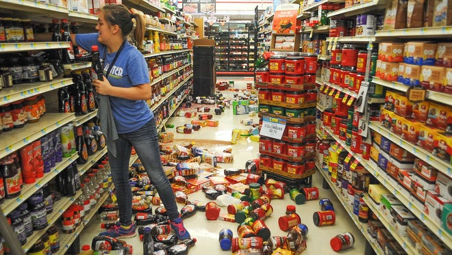 Employee Talia Pershall, 16, puts syrup back on a shelf while cleaning up at White's Foodliner grocery store Saturday, Sept. 3, 2016 in Pawnee, Okla., following a 5.6 magnitude earthquake that hit just after 7 a.m., in north-central Oklahoma.