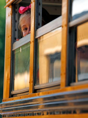 A girl peeks out a school bus window in this file photo.