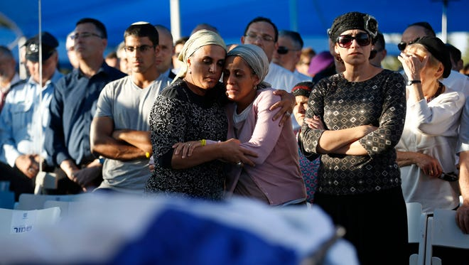 Bat-Galim Shaer, right, and Iris Yifrah, center, mothers of two of the three Israeli teens who were abducted and killed, attend the joint funeral of their sons July 1, 2014, in Modiin.