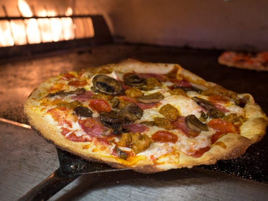 Pizzas are made to order at Fired Pie. Emilio Zazeta (kitchen manager) checks a pizza in the oven, August 4, 2014, at Fired Pie, 2855 W. Ray Road, Chandler.