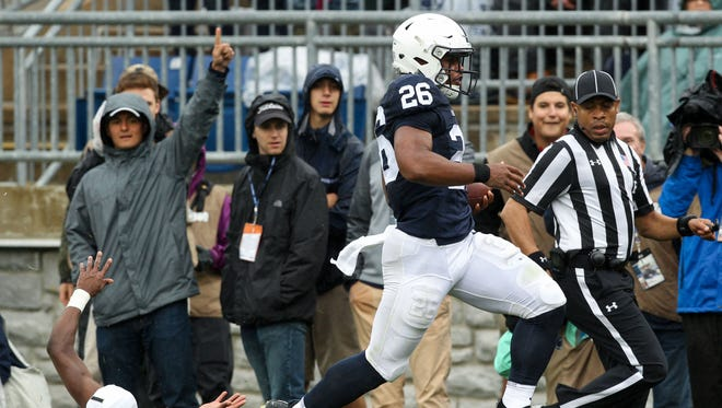 Penn State running back Saquon Barkley breaks tackles and heads for the end zone.
