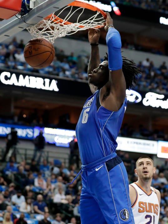 Dallas Mavericks forward Johnathan Motley (6) dunks as Phoenix Suns center Alex Len (21) watches in the first half of a NBA basketball game in Dallas, Tuesday, April 10, 2018. (AP Photo/Tony Gutierrez)