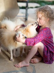 Vivienne Johnson, Sandy Giles' granddaughter, plays with her two rescue dogs.
