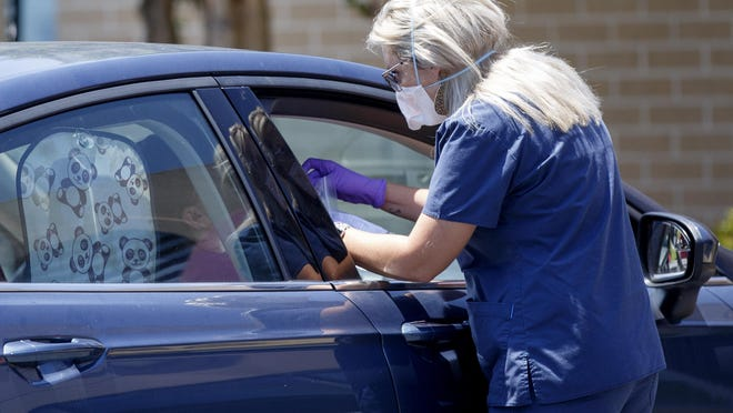 Nurse Melissa Bailey collects a sample at DeKalb Regional Medical Center's drive thru COVID-19 testing site on Thursday, July 16, 2020 in Fort Payne, Ala.