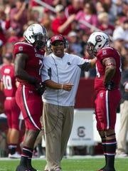 South Carolina defensive line coach Deke Adams, center,