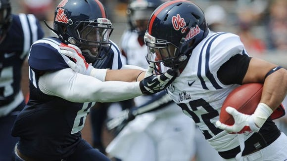 Ole Miss safety Chief Brown locks up with running back Jordan Wilkins during this year's Grove Bowl.