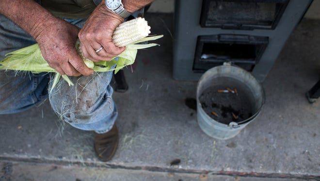 """Joe Waldroup shucks corn while sitting with friends outside Time-Out gas station in Robbinsville on Aug. 27. Waldroup is a former moonshiner and now works construction in the area. """"The smartest people that come from Graham County are the ones who graduated and got out of here,"""" Waldroup said."""