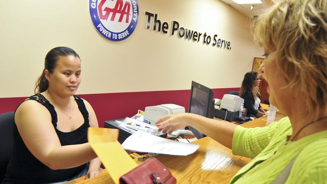 In this file photo, Guam Power Authority cashier Nadine Cruz, left, accepts a utility payment from customer Marla Baldwin. Residents can expect a 10 percent increase in their bills starting Feb. 1.