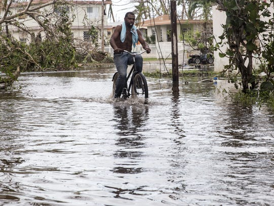 A man rides a bike through high water in Loiza, Puerto