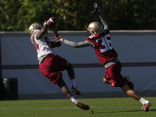 FSU's Adarius Dent catches a pass over Aaron King during spring practice at the Al Dunlap Training Facility on Wednesday, March 21, 2018.