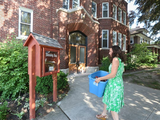 Amy Cavalier, administrator of a Buy Nothing group in a Beechwood, Homestead Heights, and Culver-Winton neighborhood, takes donated foods to the Blessing Box at the Covenant United Methodist Church on Culver Road in Rochester Thursday, June 22, 2017.