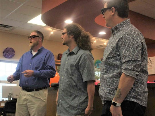 From left, Mark Yeager, Tim Masters and Ian Wilson react to seeing the world in color for the first time thanks to specially-engineered glasses.