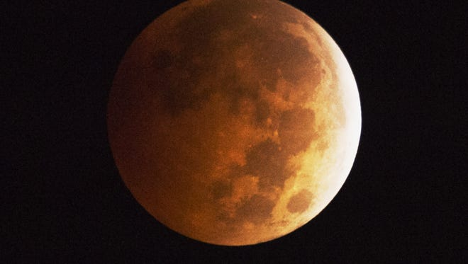 The moon appears to be to have an orange-red hue as the earth's shadow covers the moon during a total lunar eclipse, in Griffith Park in Los Angeles, California October 8, 2014. A total lunar eclipse is sometimes called a blood moon because of the red color that is cast upon it by light refracting in Earth's atmosphere.   AFP PHOTO / Robyn BeckROBYN BECK/AFP/Getty Images ORG XMIT: 517318833 ORIG FILE ID: 534198961