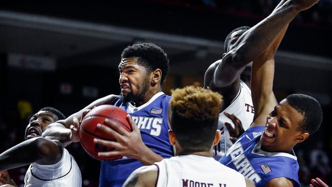 While grabbing a rebound University of Memphis forward Dedric Lawson (middle left) is fouled, as teammate Jimario Rivers (right) gets pushed on the play during second-half action against Temple University at the Liacouras Center in Philadelphia. The Tigers lost the game 77-66.
