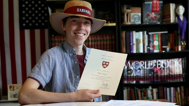 Dylan Parker in his study at his Pittsford home with expectancy letters from schools around the country. Dylan was accepted into seven of the eight Ivy League schools and picked Harvard as his college of choice.