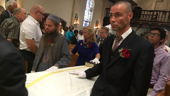 Kenny Irwin Jr. (center) walks with the casket of his dad, Ken Irwin Sr. during Mass at Our Lady of Solitude Catholic Church in Palm Springs on Wednesday, July 6, 2016.