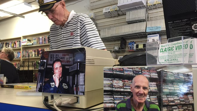 Bob Hyatt works the counter at Hyatt's Classic Video. In the foreground are photos of him when he started in the hi-fi stereo business in the 1960s and today.