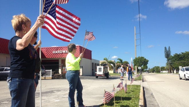 Supporters of the American flag gather outside of Family Hardware in Cape Coral on Friday.  Cape code enforcement asked the business to take down flags put out by an associate because they are in the right of way.  An associate at the store erected the flags in honor of his family. As of right now,  they have no intention of taking the flags down.
