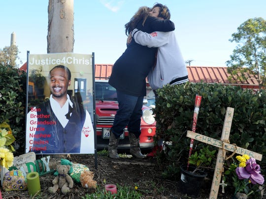 Rene Camper Stewart, left, hugs Norma Barrera in December at the roadside memorial for Christopher Camper near a bus stop on North Ventura Road in Oxnard.