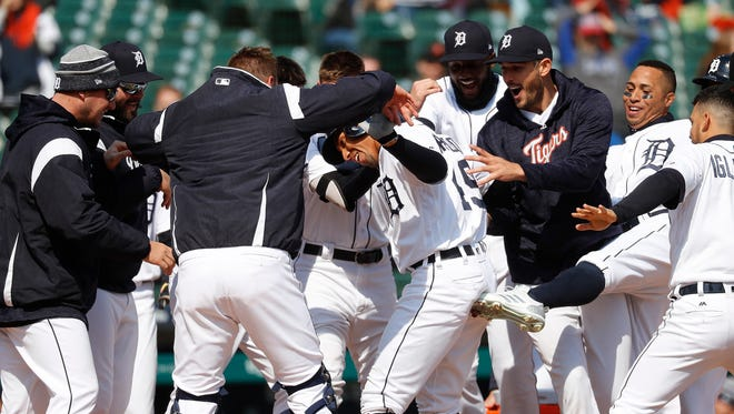Tigers second baseman Dixon Machado, center, is congratulated for his walk-off solo home run in the ninth inning of the Tigers' 6-5 win over the Orioles on Wednesday, April 18, 2018, at Comerica Park.
