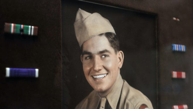 Clarence Derrington keeps a photograph of himself in his World War II uniform on the wall of his home.