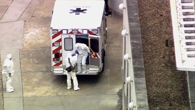 An ambulance arrives Saturday with Ebola victim Dr. Kent Brantly, right, at Emory University Hospital in Atlanta. Brantly was infected with the Ebola virus in Africa.