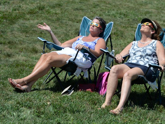 Tracy Smith and Kim Metje watch Monday's partial solar