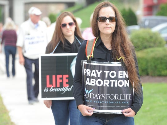 Two women, both who refused to give their names, walk with others from 40 Days for Life protesting the Planned Parenthood clinic on Oneida Street.