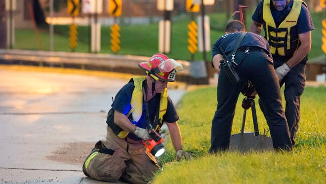 In this June 30, 2014 photo Cedar Rapids firefighters open a storm sewer cover as they search for a teenager who was swept away in a storm drain after heavy rainfall overwhelmed the eastern Iowa city's storm sewer system. Officials say Logan Blake, 17, was swept away by the fast-moving water in the drain at an elementary school around 7:20 p.m. Monday. (AP Photo/The Gazette-KCRG, Liz Martin)