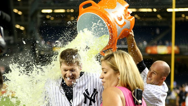 Chase Headley gets a bath by teammate Brett Gardner after his single won the game 2-1 over the Rangers in the 14th inning on Tuesday.