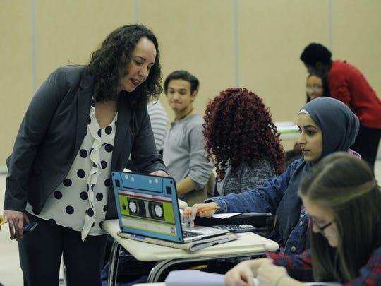 Jennifer Newman, head of Oakland Early College, talks to 10th-grader Sana Ishaqsei during class.