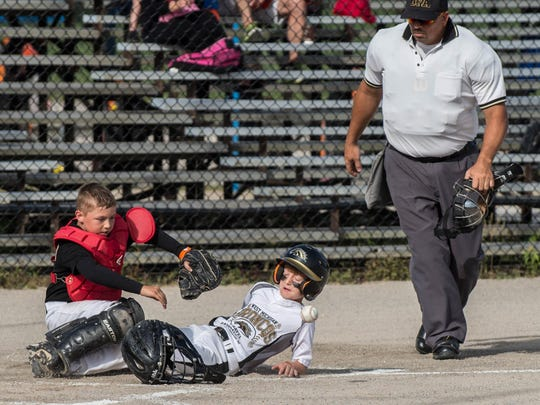 Robert Darrow of the West Michigan Broncos (9-under) slides into home during first round tournament action at the BPA World Series at Bailey Park.
