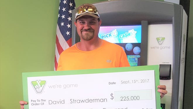 David Strawderman, of Lyndhurst, holds up his Virginia Lottery check for $225,000.