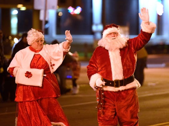Santa and Mrs. Claus wave to the crowd Saturday during the 2015 Winter Nights and Lights parade in downtown St. Cloud